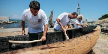 Arkeologlar taş baltalarla taş devri teknesi yontuyorlar